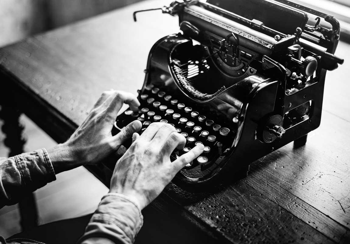 someone typing on an old typewriter